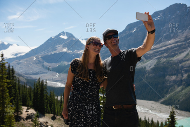Couple taking selfie with mobile phone at countryside