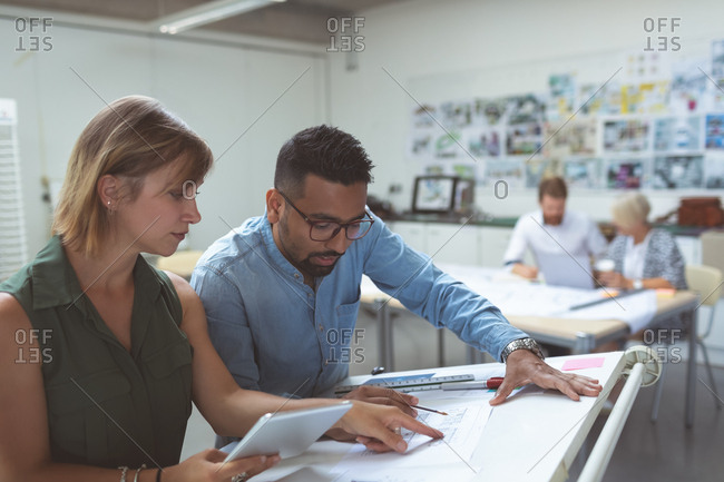 Executives discussing over blueprint on drafting table in office