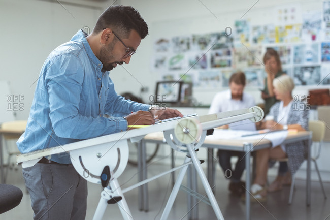 Male executive working over drafting table in office