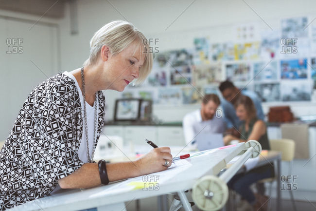 Female executive working on drafting table in office