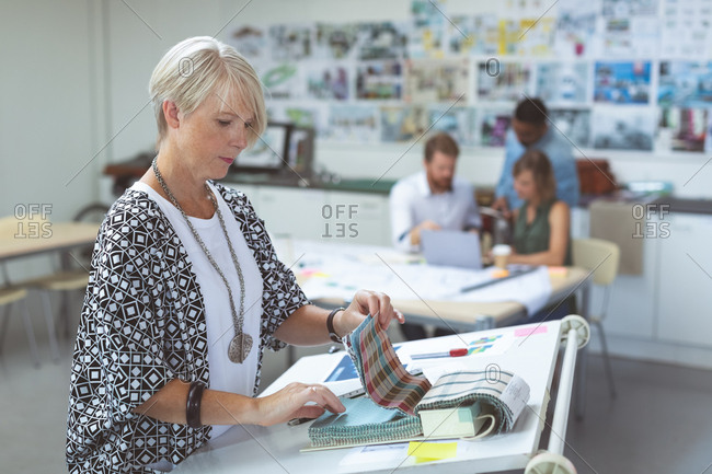 Female executive checking catalog on drafting table in office