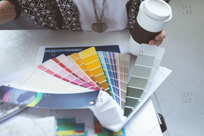 Close-up of female executive checking color swatch on drafting table in office