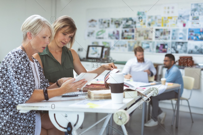 Female executives discussing over digital tablet on drafting table in office