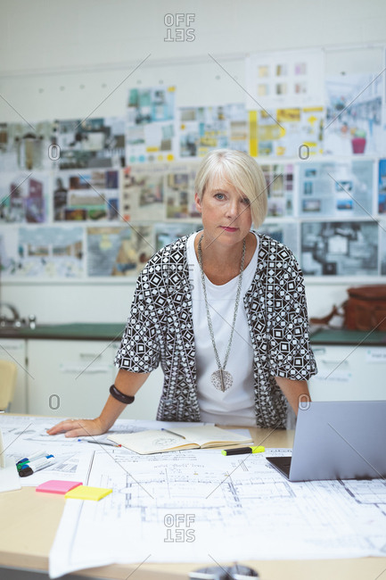 Portrait of female executive standing at desk in office