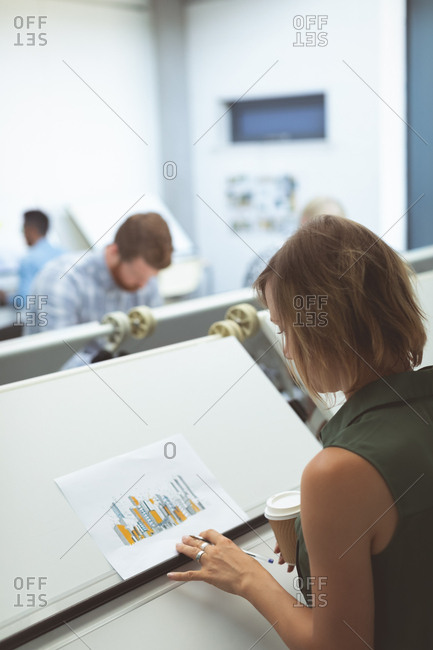 Female executive looking at blueprint on drafting table in office
