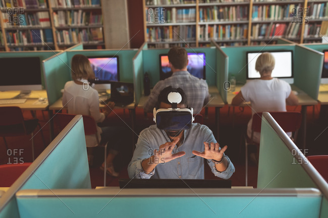 Executive using virtual reality headset at desk in office