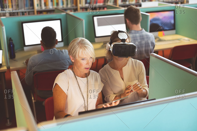 Female executives using virtual reality headset and digital tablet at desk in office