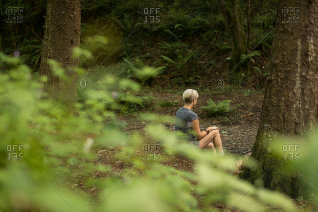 Thoughtful woman relaxing in the forest