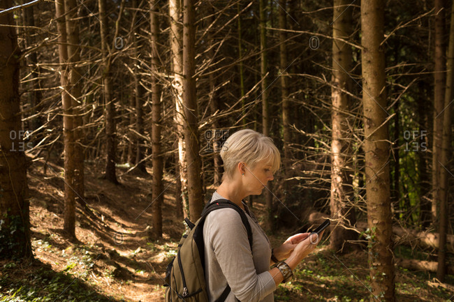 Side view of woman using mobile phone in the forest