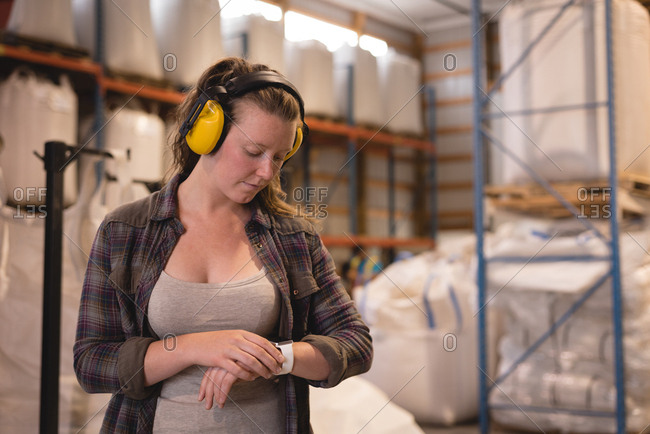 Female worker checking time on smart watch at warehouse