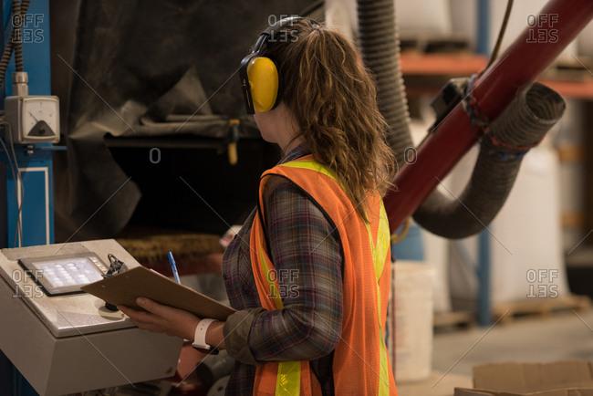 Female worker operating machine at warehouse