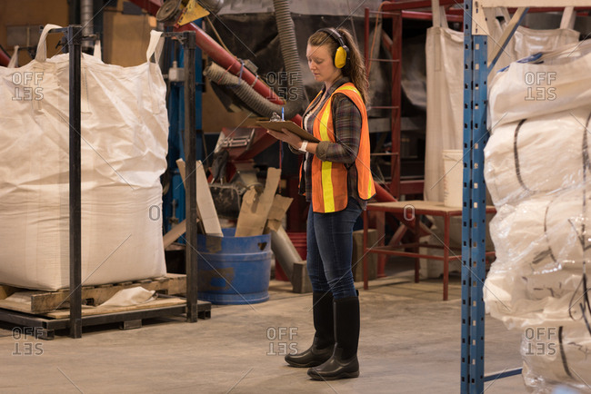 Female worker writing on clipboard in warehouse