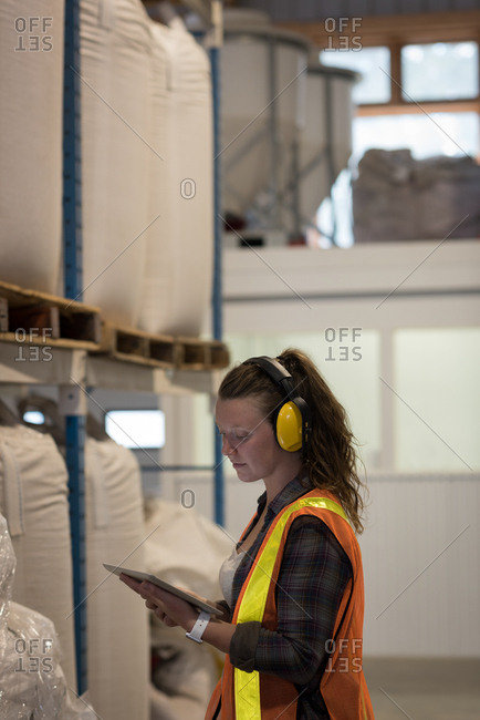 Beautiful female worker using digital tablet in warehouse