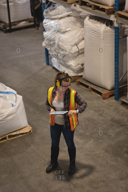 Female worker checking time while using digital tablet at warehouse