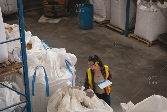 Female worker with digital tablet checking grains at warehouse