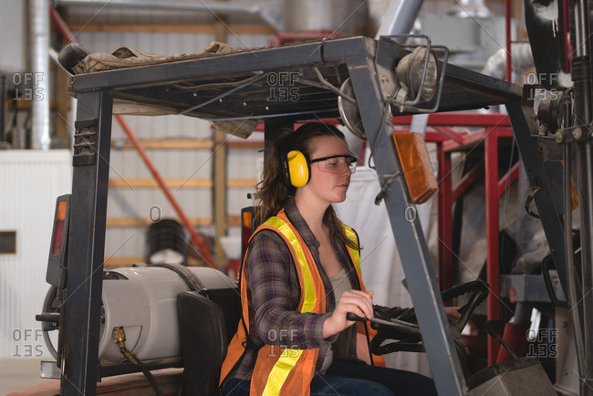 Female worker driving forklift at warehouse