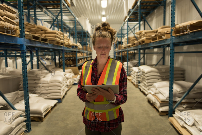 Female worker using digital tablet at warehouse