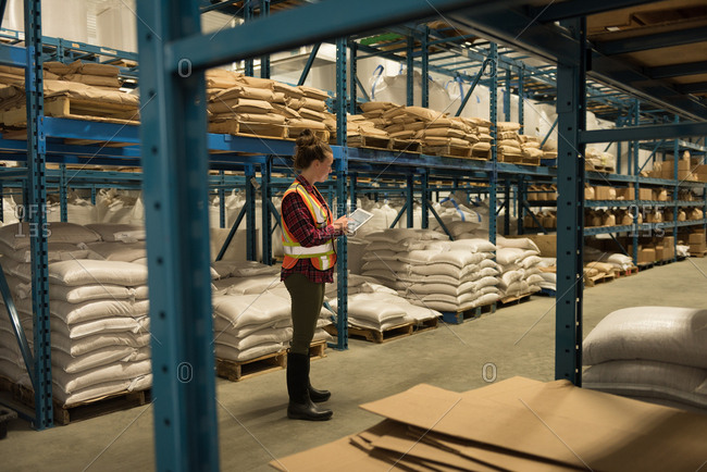 Side view of female worker using digital tablet at warehouse