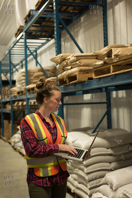 Beautiful female worker using laptop at  warehouse