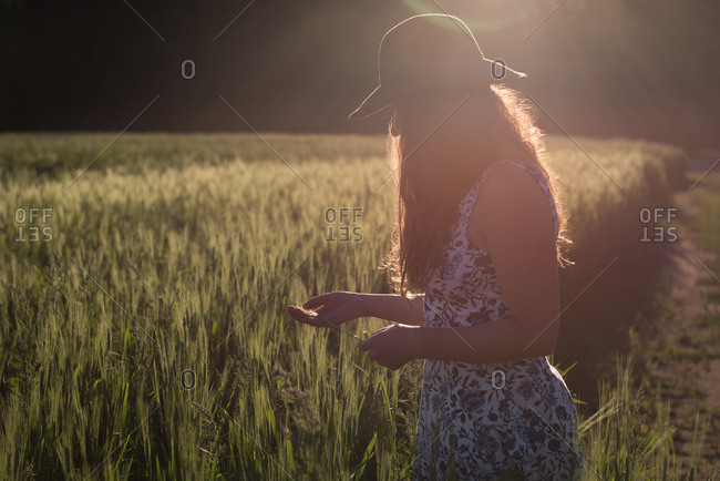Woman holding crops in the field on a sunny day