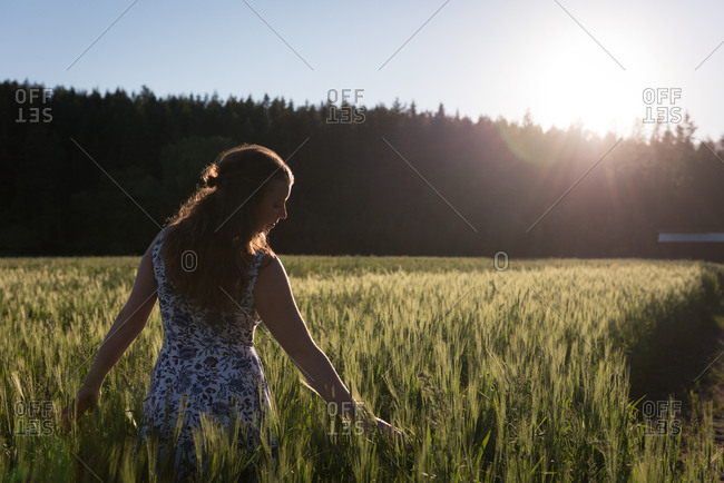 Woman touching crop in the field on a sunny day