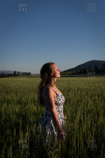 Beautiful woman standing with eyes closed in the field