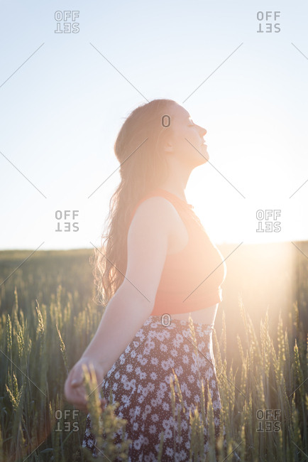 Young woman standing with arms outstretched in the field