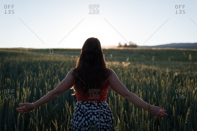 Rear view of woman standing with arms outstretched in the field