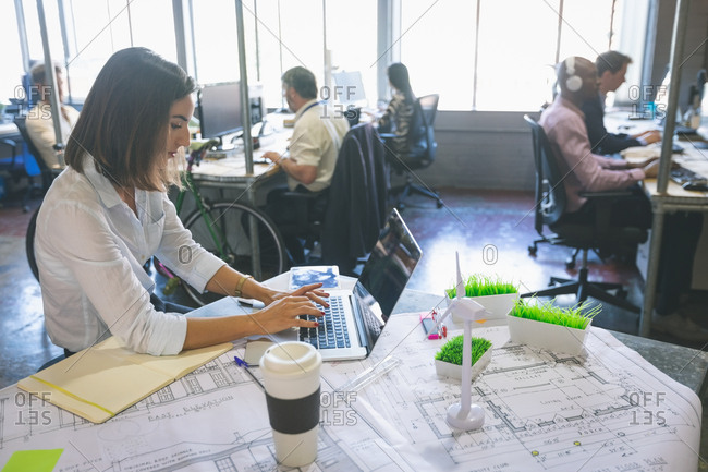 Female executive using laptop at desk in office