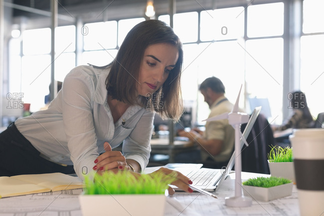 Female executive looking at windmill model in office