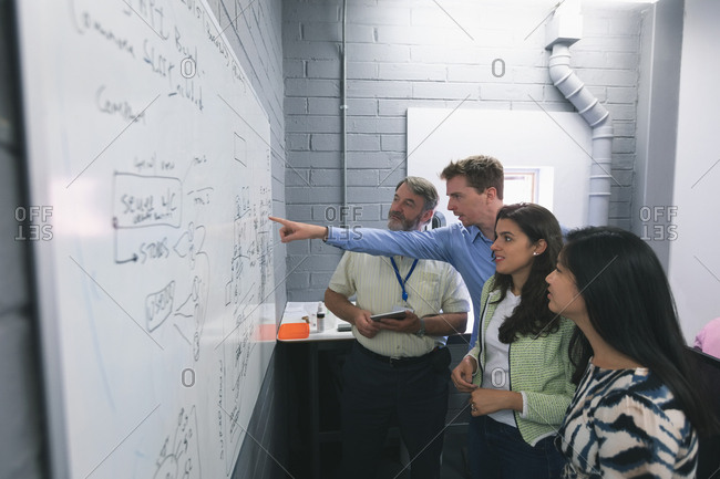 Business people discussing over whiteboard in office