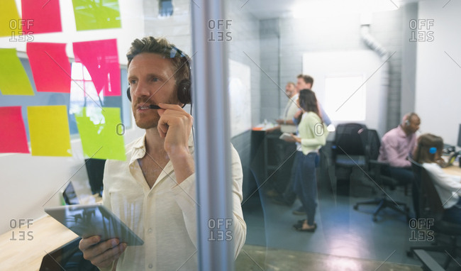 Male executive looking at sticky notes in office
