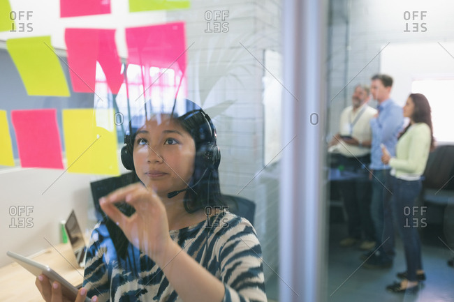 Female executive looking at sticky notes in office