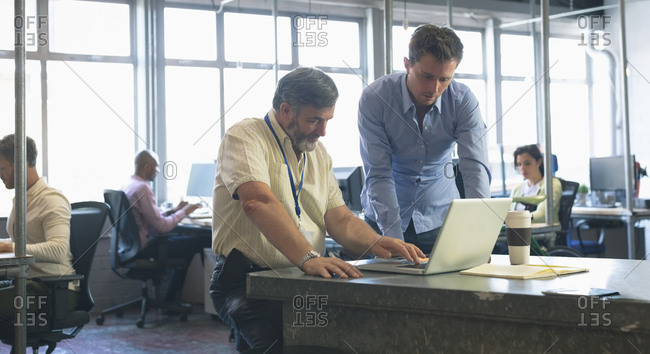 Business colleagues discussing over laptop in office