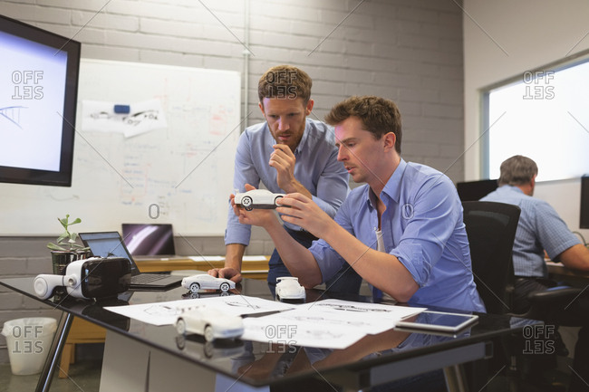 Business colleagues discussing over car model in office