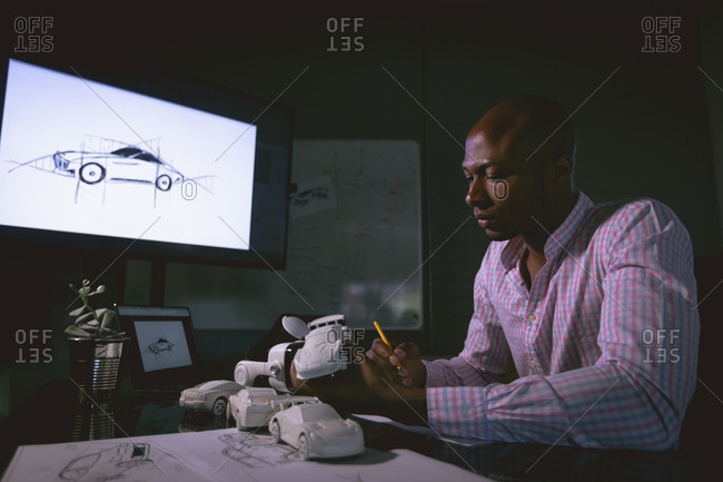 Male executive examining a car model in office