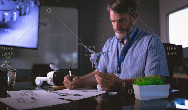 Male executive examining a windmill model in office