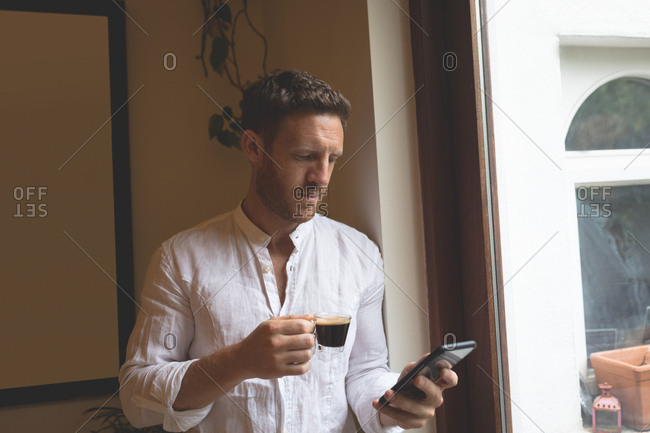 Man using mobile phone while having black coffee at home