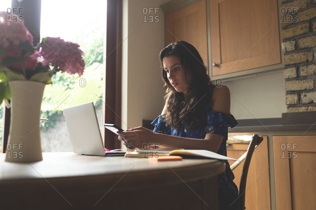 Beautiful woman using mobile phone at home