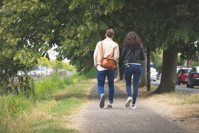 Rear view of couple walking on street in the city