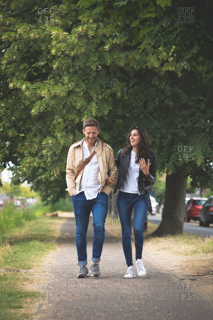 Happy couple interacting while walking in street