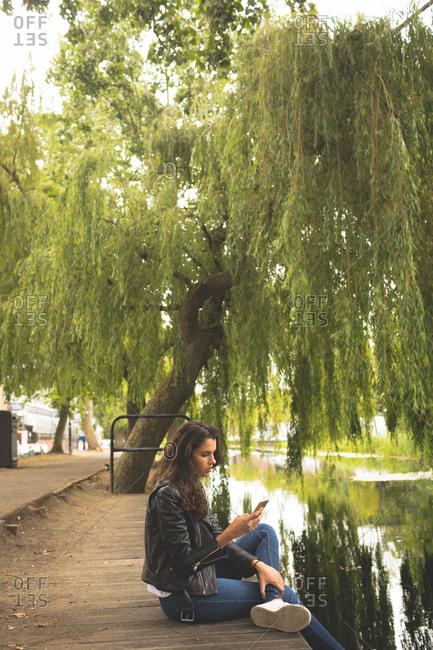 Beautiful woman using mobile phone while sitting near lake side