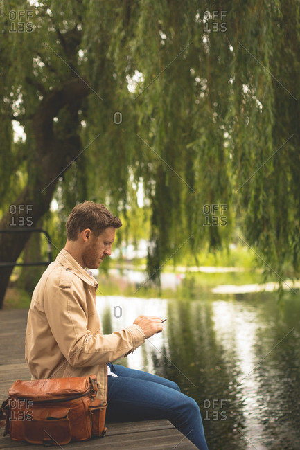 Side view of man using digital tablet near lake side