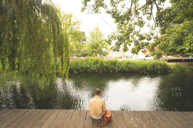 Rear view of man sitting near lake side