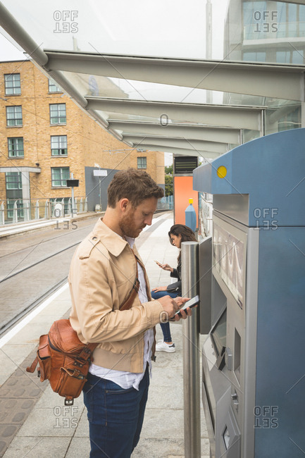 Side view of man using mobile phone while standing in platform