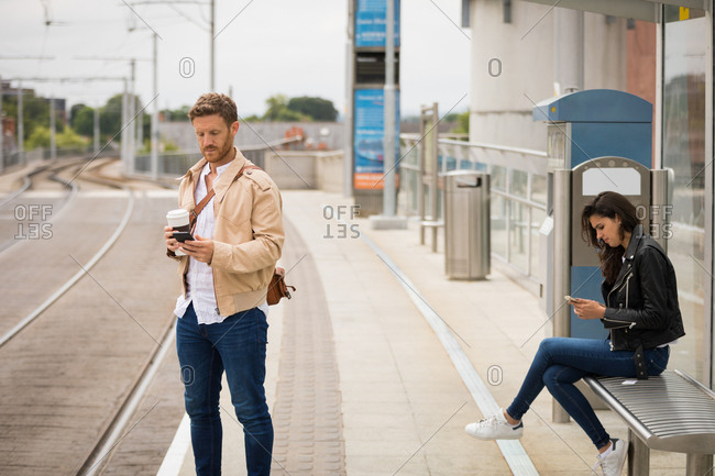 Commuter using mobile phone in platform at railway station