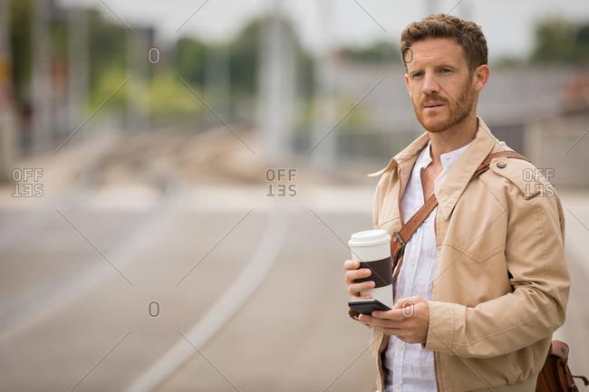 Smart man using mobile phone in platform at railway station