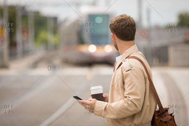 Man using mobile while looking at train in platform