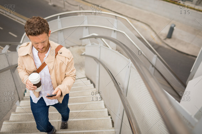 Smart man walking up stairs while using mobile phone