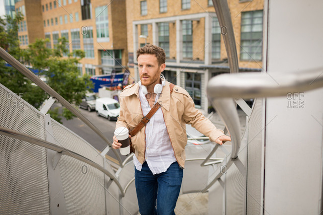 Smart man walking up stairs in city